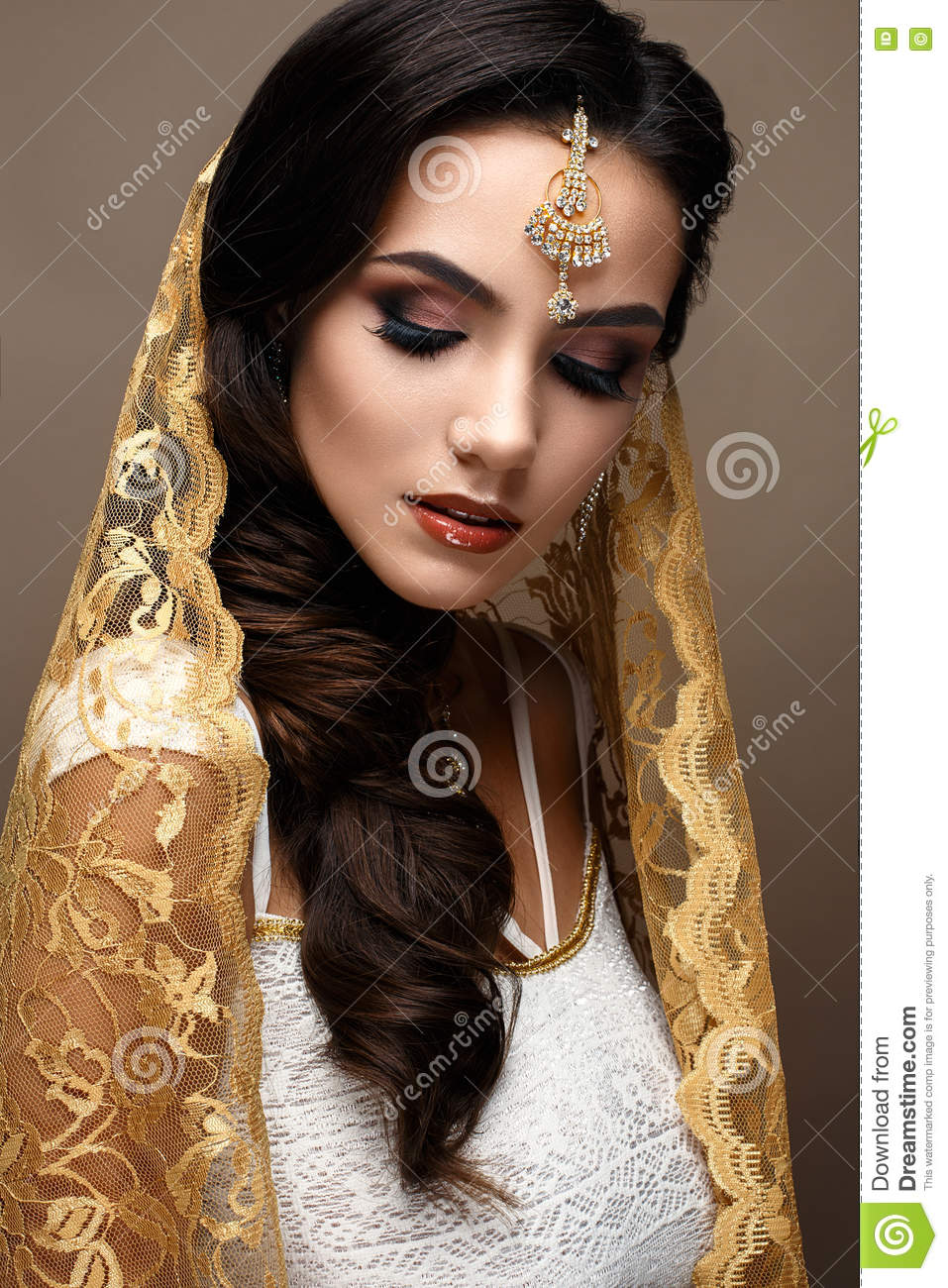 Beautiful girl in Indian style with a scarf on her head. Model with a creative and bright makeup. Beautiful face. The photo was taken in a studio.