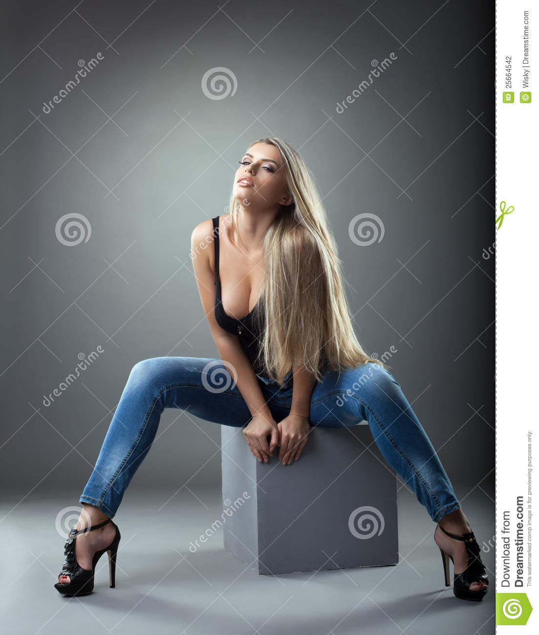 Beautiful Girl In Jeans Posing On Cube Stock Photography