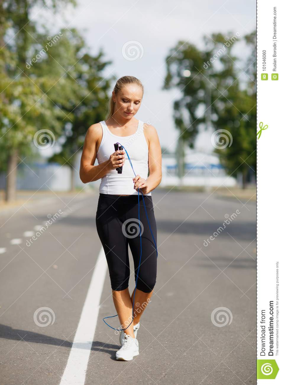 Beautiful girl with a jumping rope. Sports woman jumping on a park background. Active lifestyle concept.