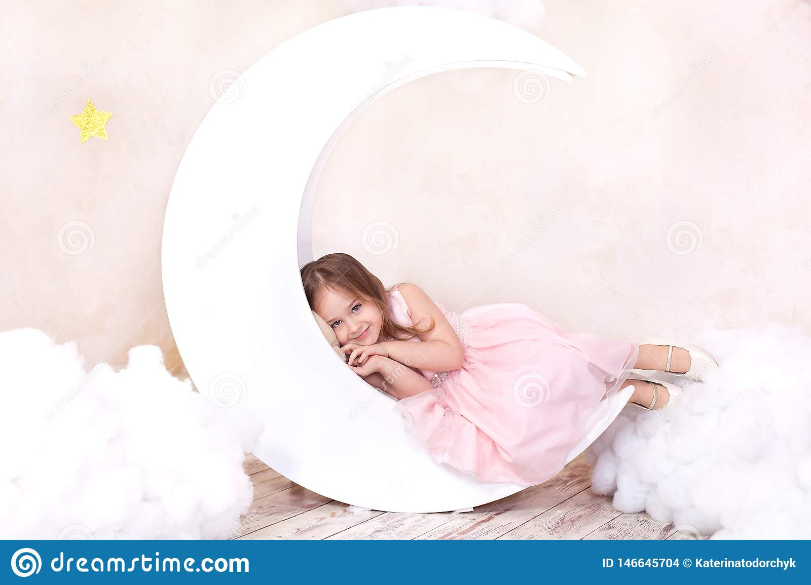 Beautiful girl lies in the studio with the decor of the moon, stars and clouds. Little girl dreaming.  Sweet dreams. Little cute g