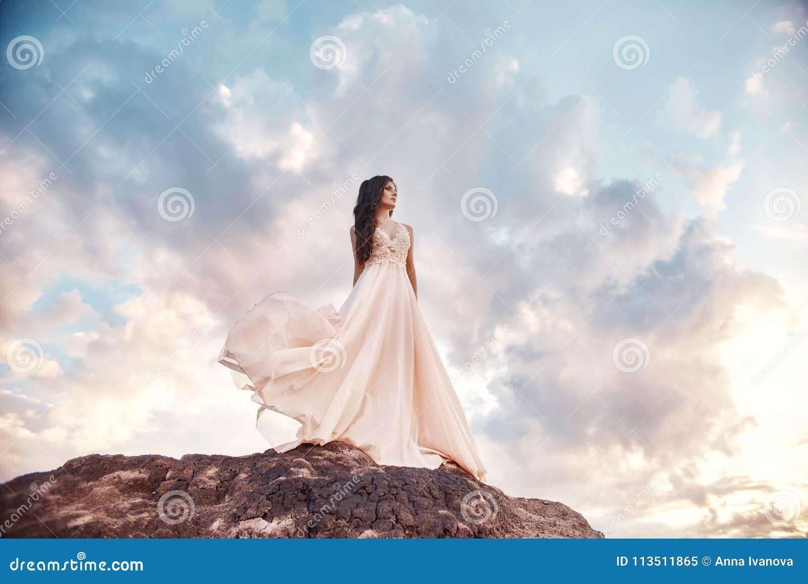 Beautiful girl in a light summer dress beige walks in the mountains. Light dress flutters in the wind, blue summer sky. Fabulous
