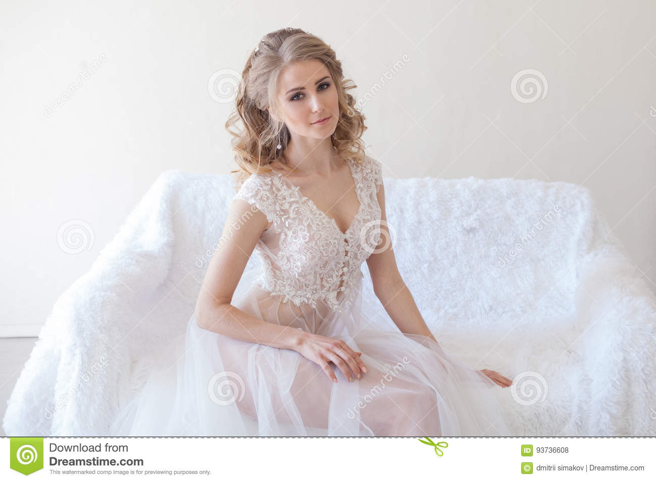 Beautiful girl in lingerie sitting on a white couch wedding