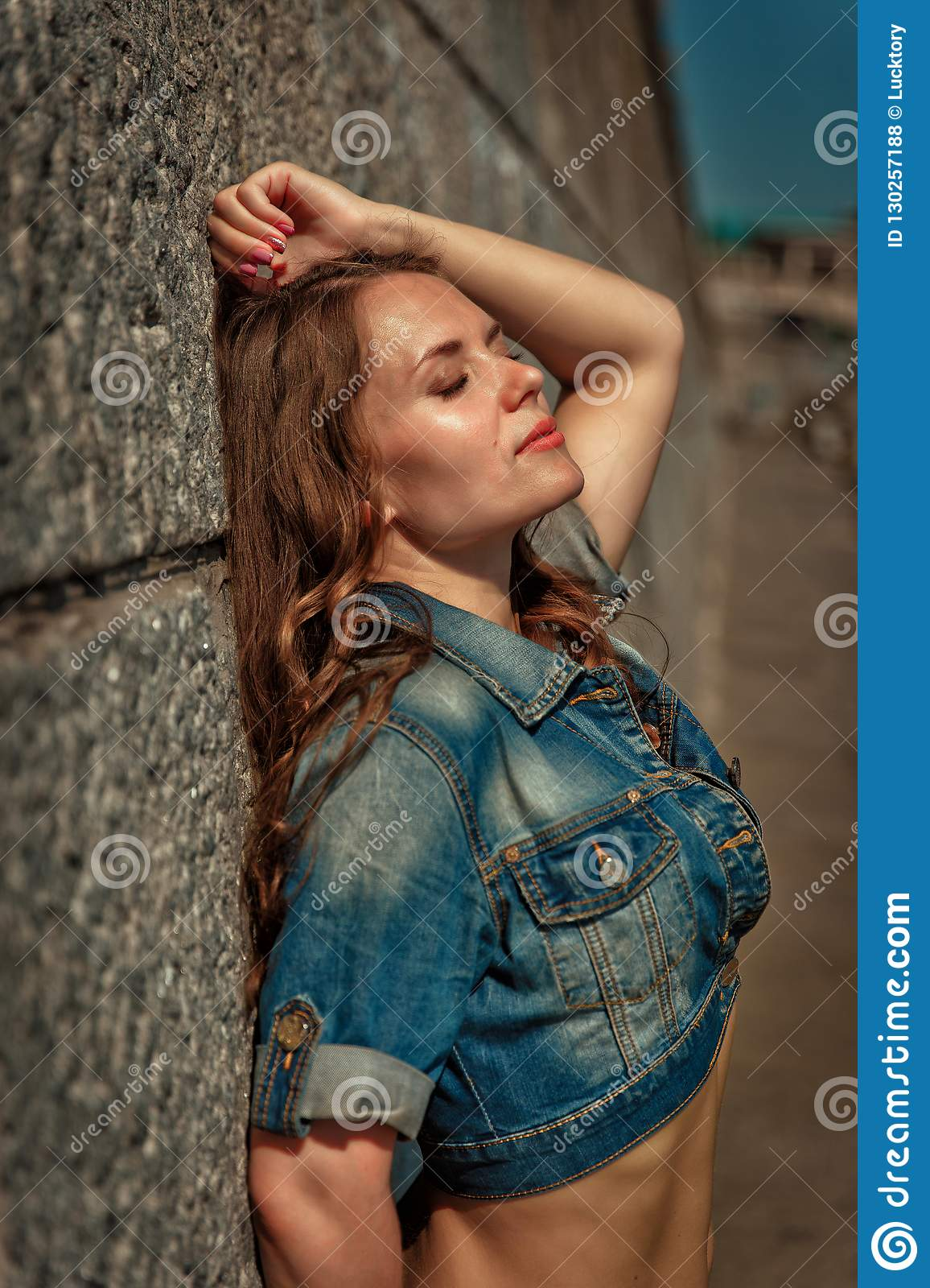 Beautiful Girl With Long Hair And In A Denim Jacket Stands Near The