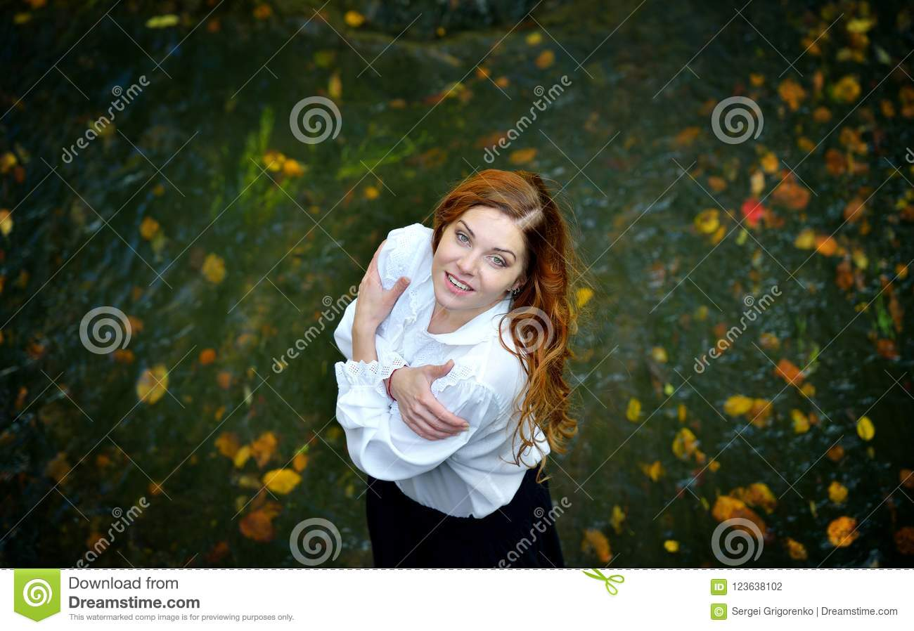 Beautiful girl with long hair in white shirt and black skirt standing in the river with autumn leaves and looking up.