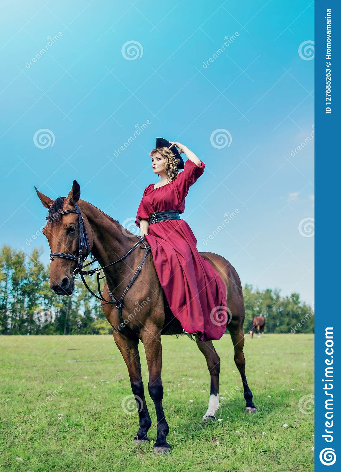 Beautiful girl in a long red dress riding a brown horse against a blue sky.