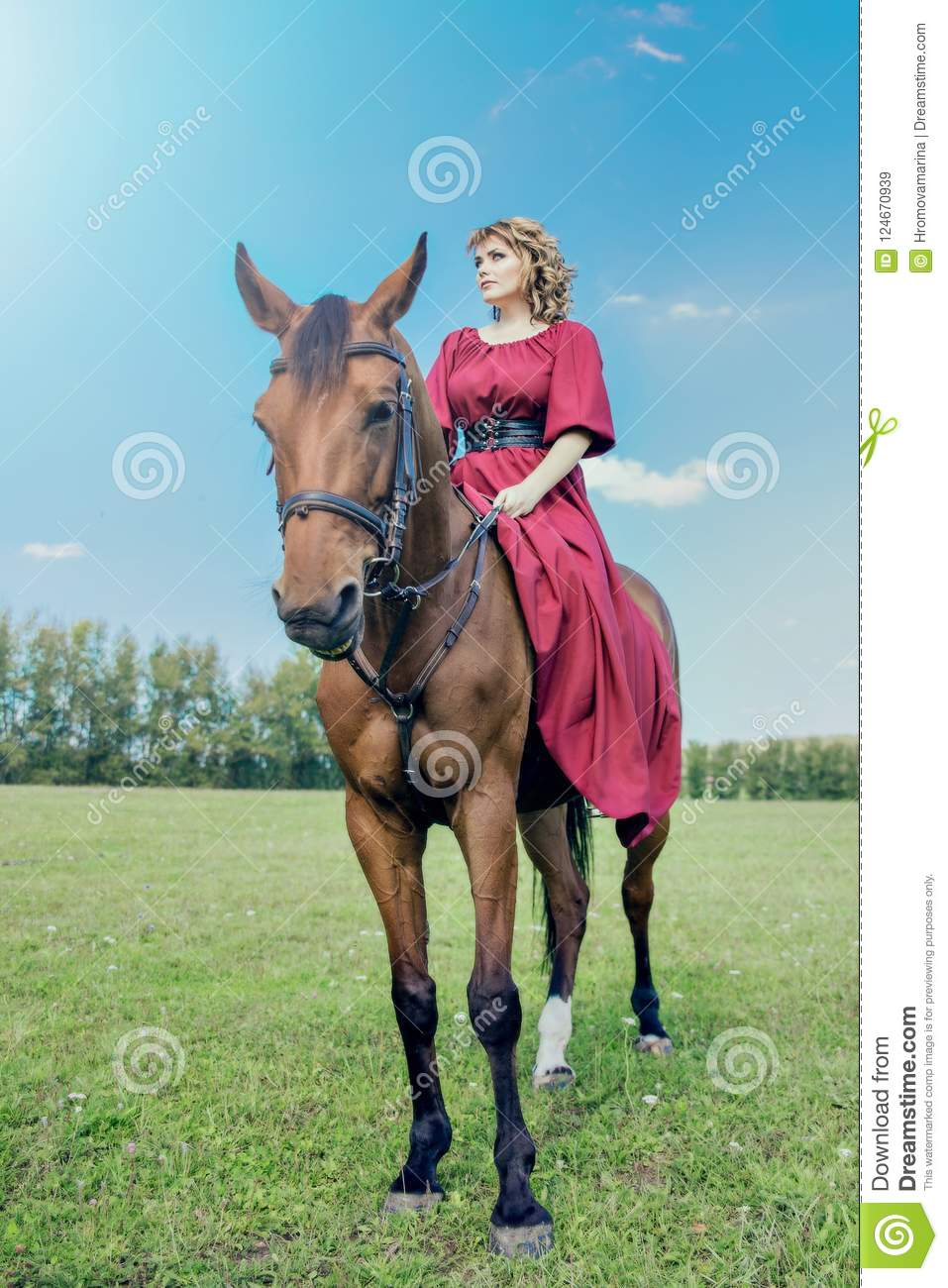 Beautiful girl in a long red dress riding a brown horse