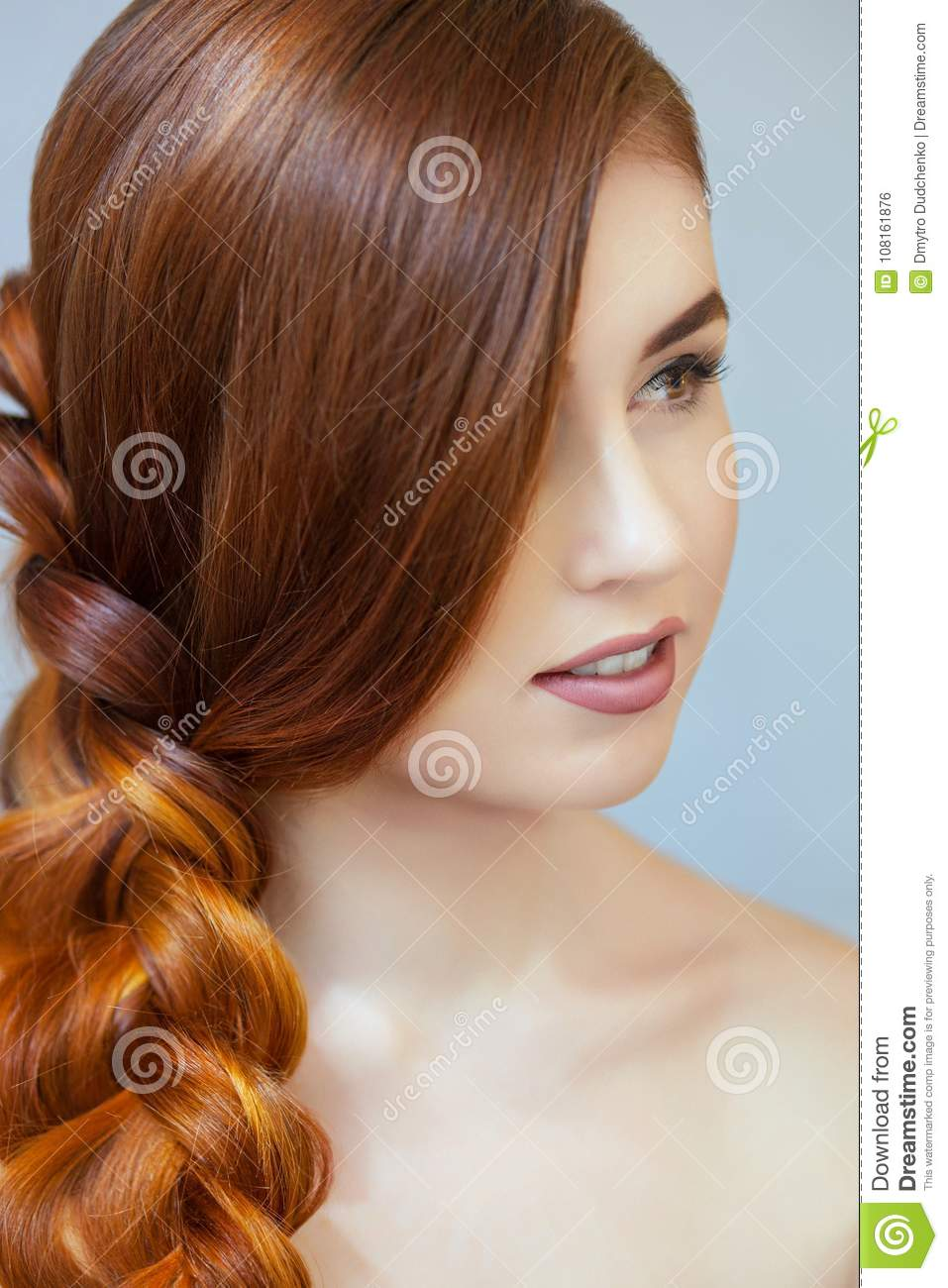 Beautiful girl with long red hair, braided with a French braid, in a beauty salon.