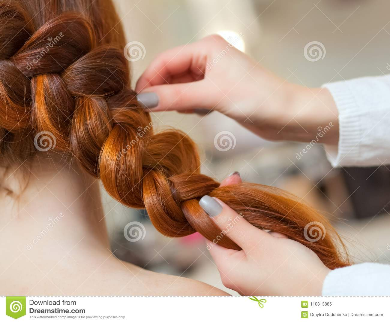 Beautiful girl with long red hair, hairdresser weaves a braid, in a beauty salon.
