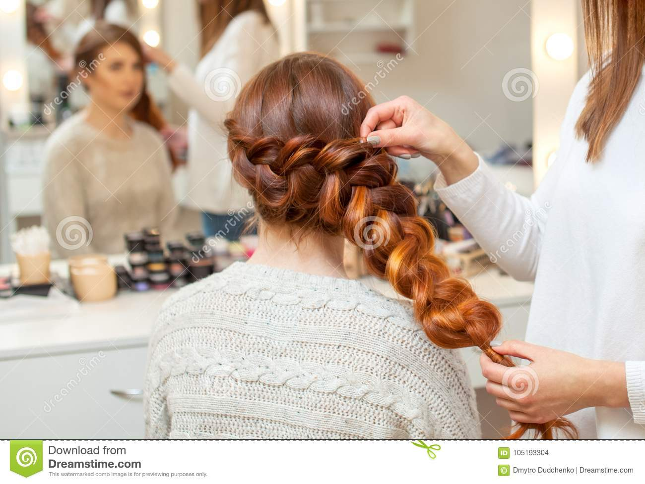 Beautiful girl, with long, red-haired hairy. hairdresser weaves a French braid, close-up