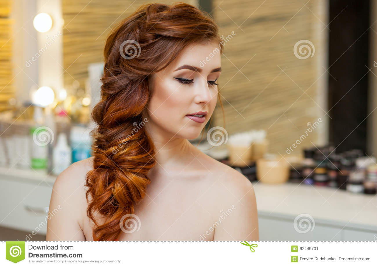 Beautiful girl, with long, red-haired hairy. Hairdresser weaves a French braid, close-up in a beauty salon