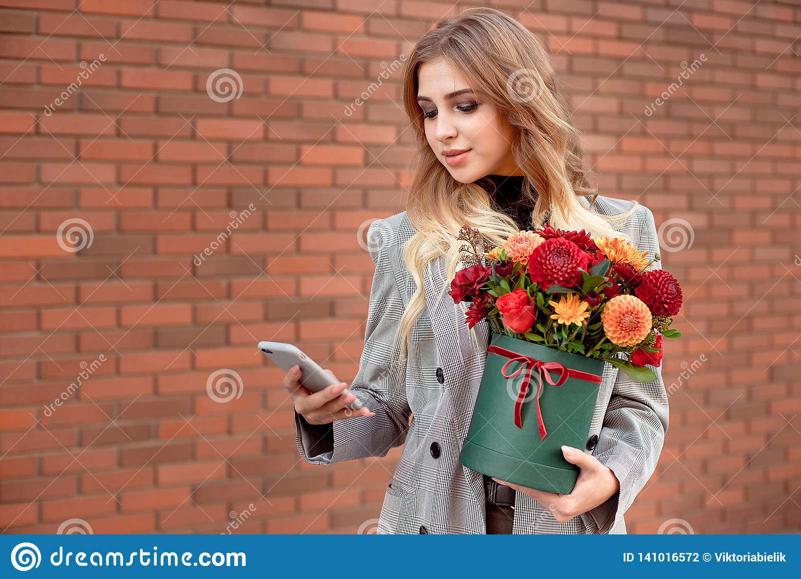 Beautiful girl looks into the phone in her hands holding a green box with bright colors.
