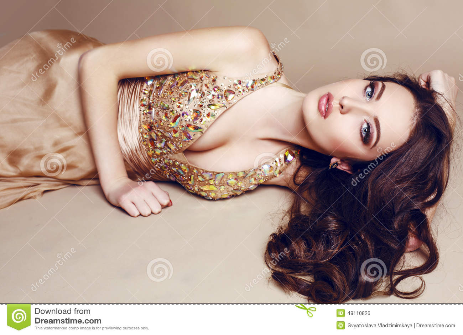 Beautiful girl with luxurious dark hair in sequin dress posing at studio