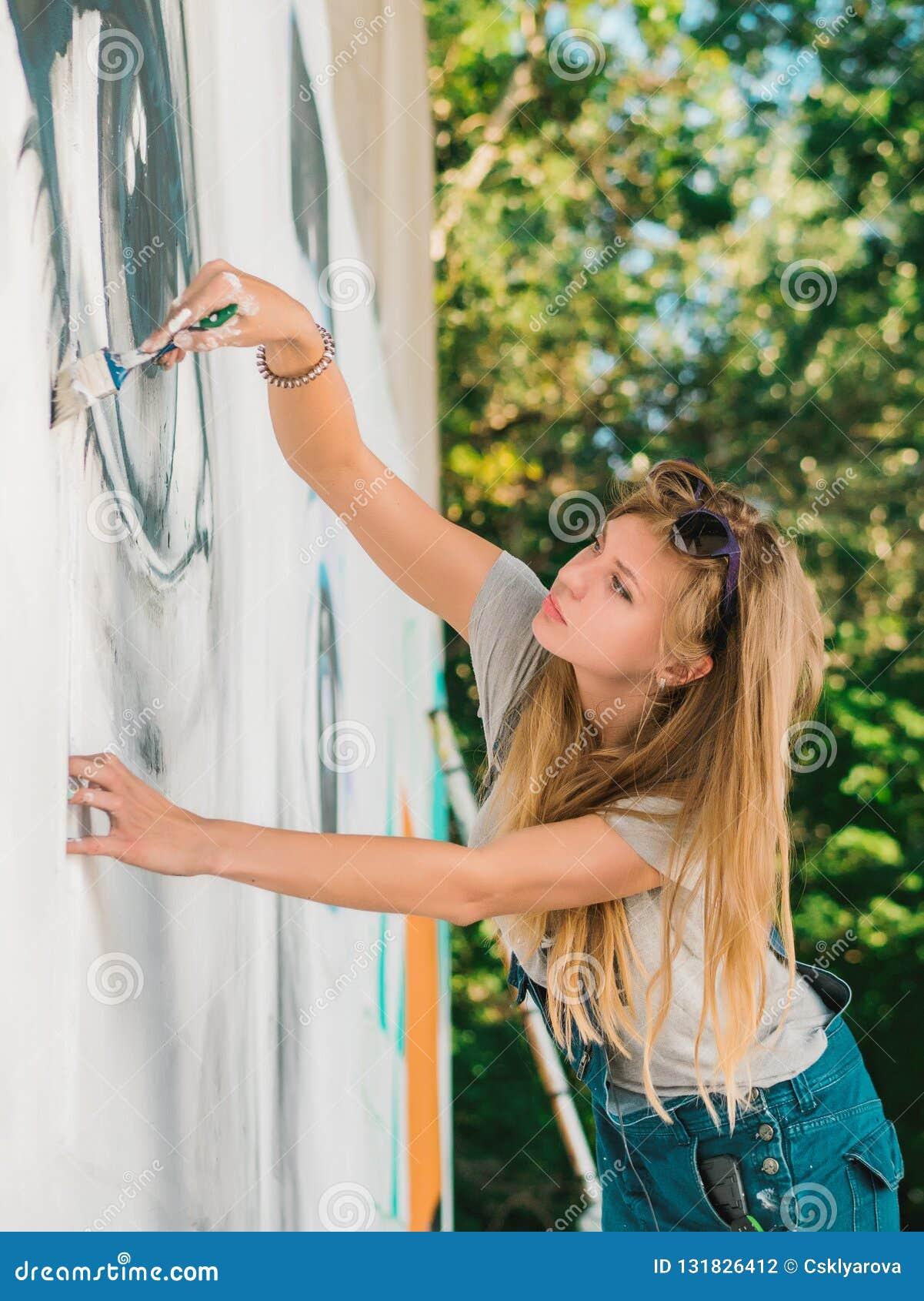 Beautiful Girl Making Graffiti Of Big Female Face With ...