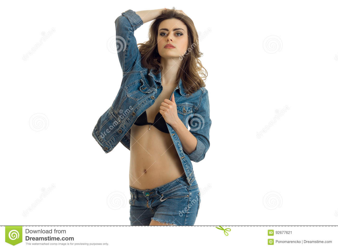 19c963d898 Beautiful girl with a naked belly and denim jacket posing lifting a hand to  head isolated on white background