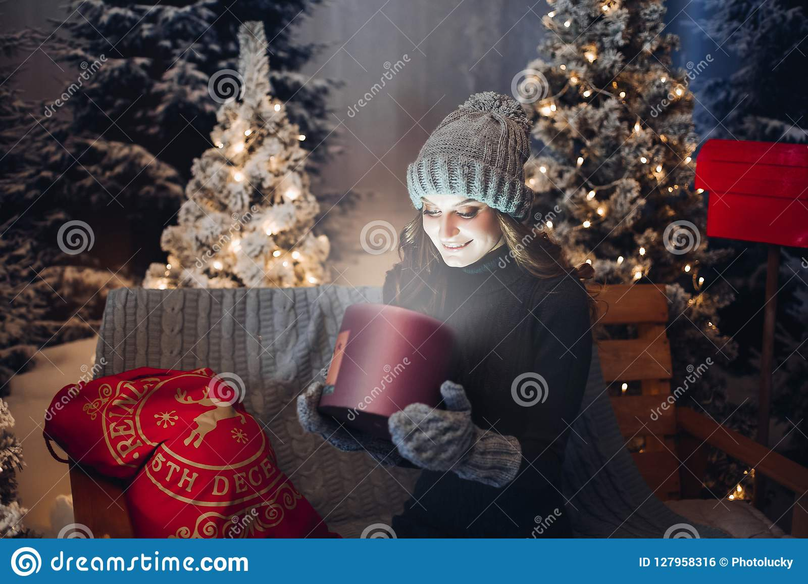 Beautiful girl opening magic box with present at Christmas night.