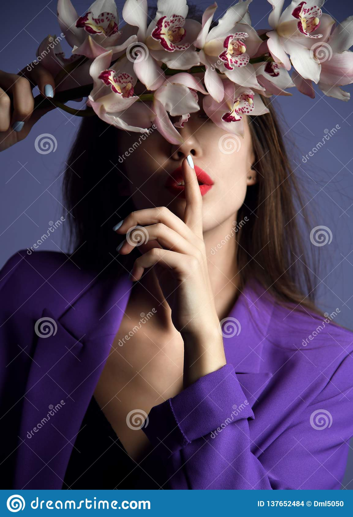 Beautiful girl with orchid flowers. Beauty model woman face on purple background