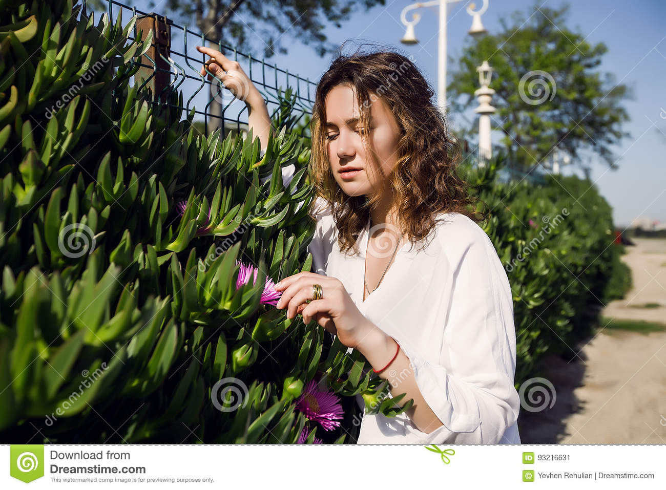 Beautiful Girl in a park, woman with curly hair.Summer sunny lifestyle fashion portrait of young stylish hipster woman,wearing cut