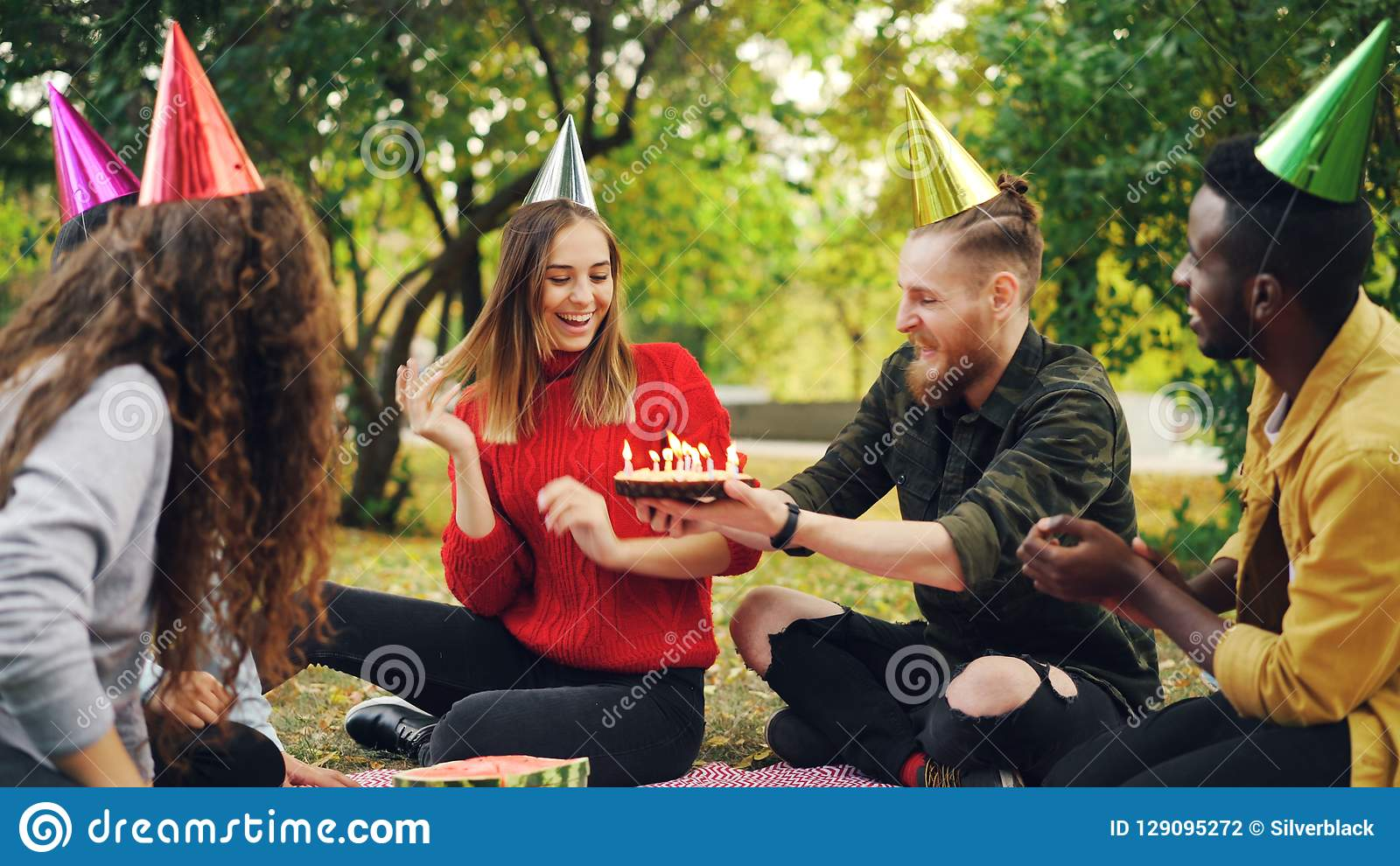 Beautiful girl in party hat is celebrating birthday with friends in park on picnic making wish, blowing candles on cake