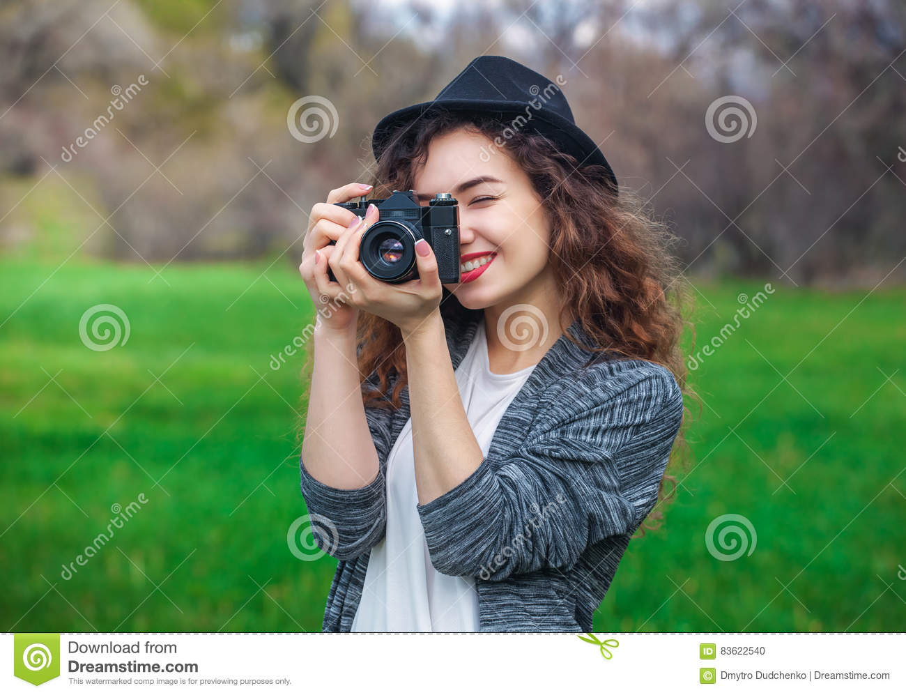 ae698afe15 Royalty-Free Stock Photo. Beautiful girl-photographer with curly hair  holding an old camera and take a picture