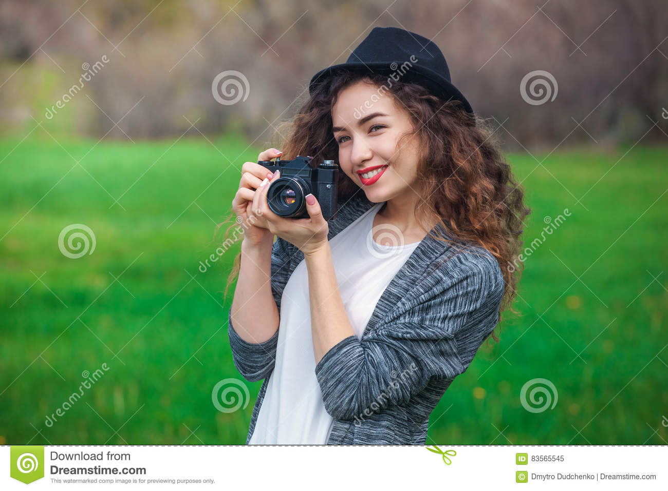 Beautiful girl-photographer with curly hair holds a camera and make a photo, spring outdoors in the park.