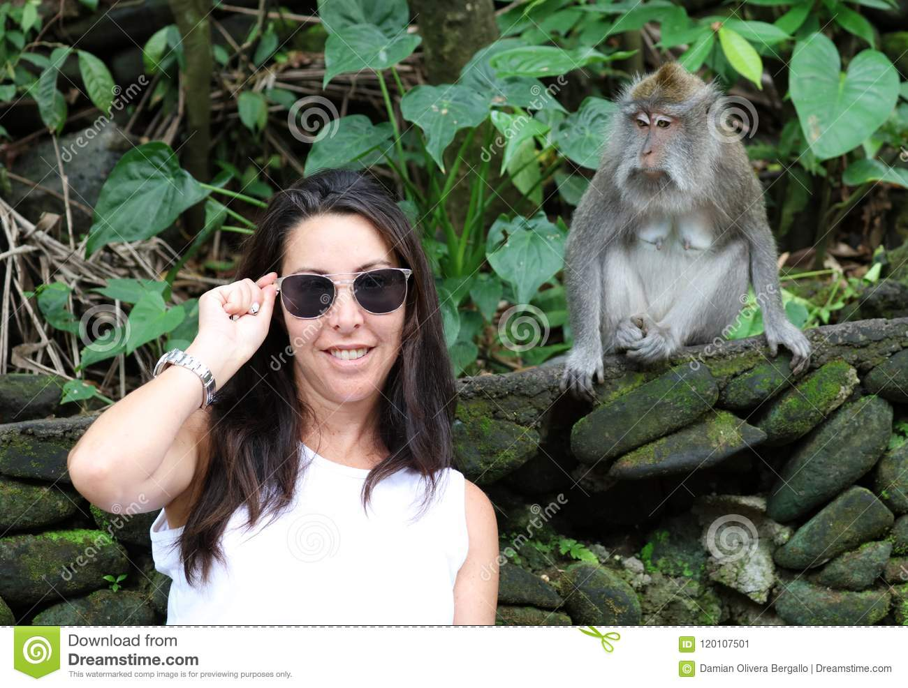 Beautiful girl playing with monkey at monkeys forest in Bali Indonesia, pretty woman with wild animal.