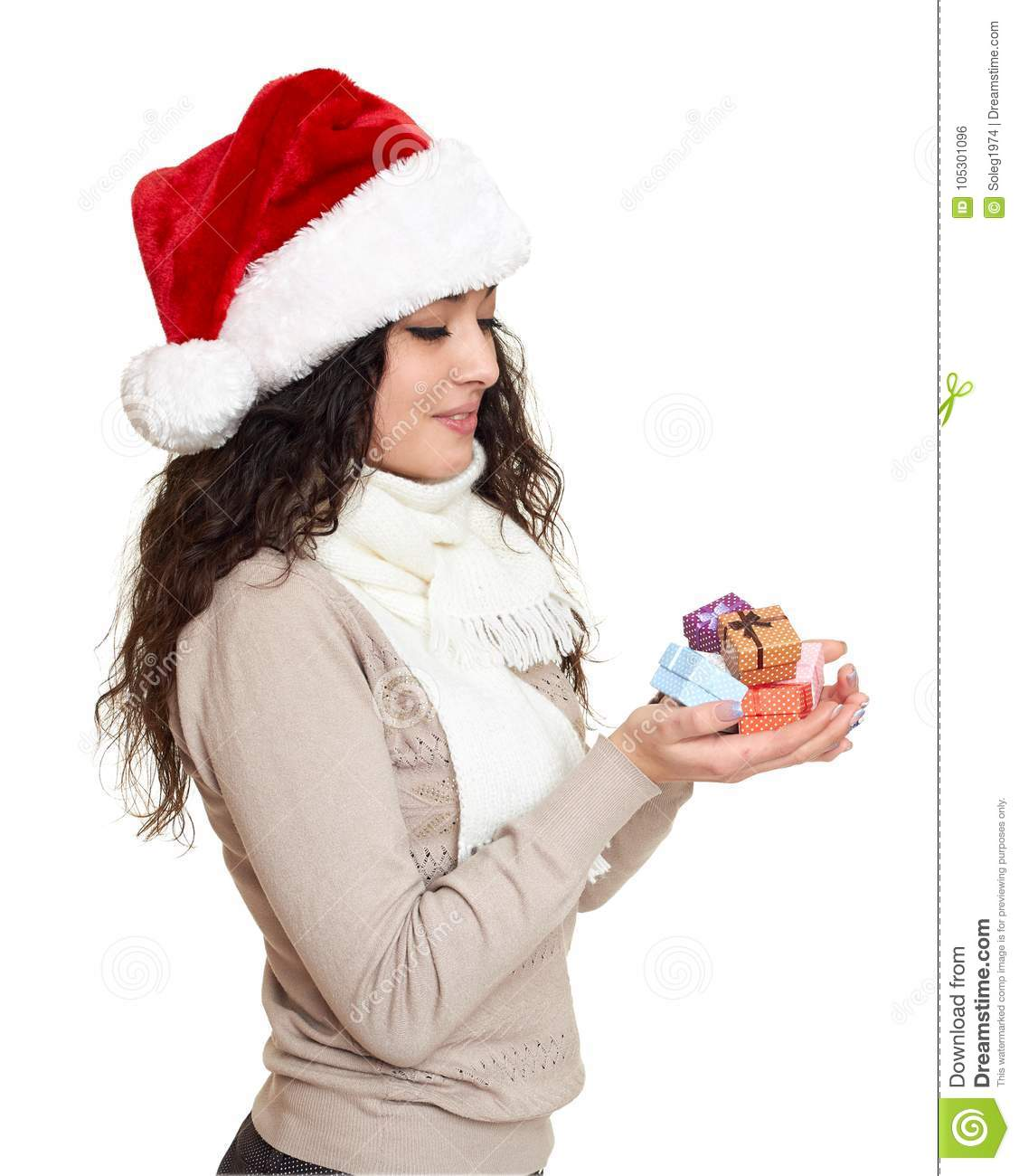 Beautiful girl portrait dressed in santa hat with handful of little gift boxes. White background. New year eve and winter