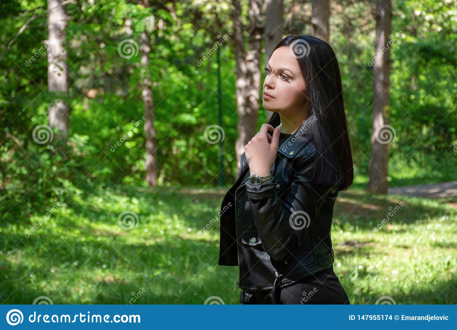 Beautiful girl portrait in the forest on a spring day. Woman with black hairstyle and wears a leather jacket
