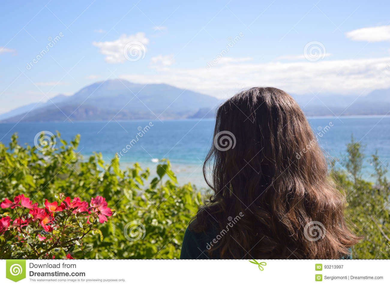 Beautiful girl posing back with natural lake mountains landscape with flowers and trees, woman model in nature