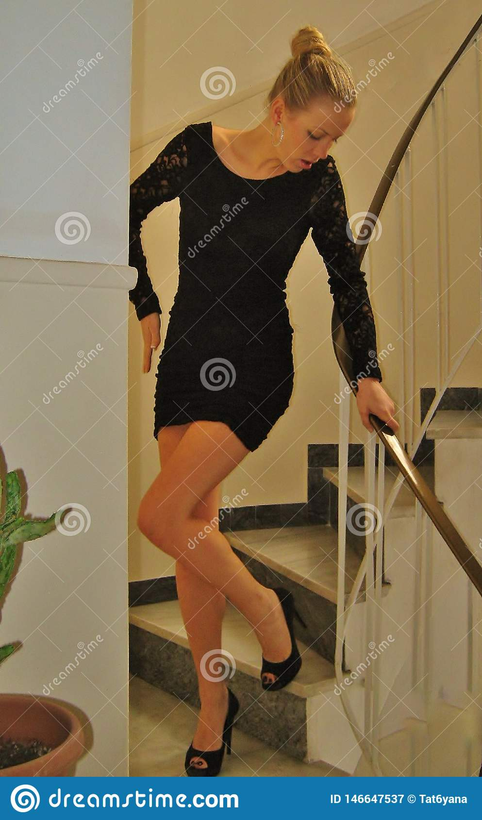 Beautiful girl posing in a black dress on the steps