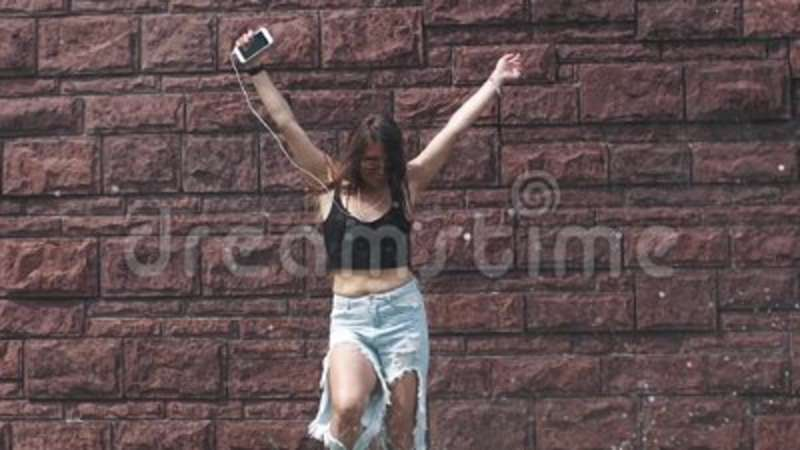 Beautiful girl in ragged jeans and sunglasses sings songs and dances under  water splashes  girl is having fun walking