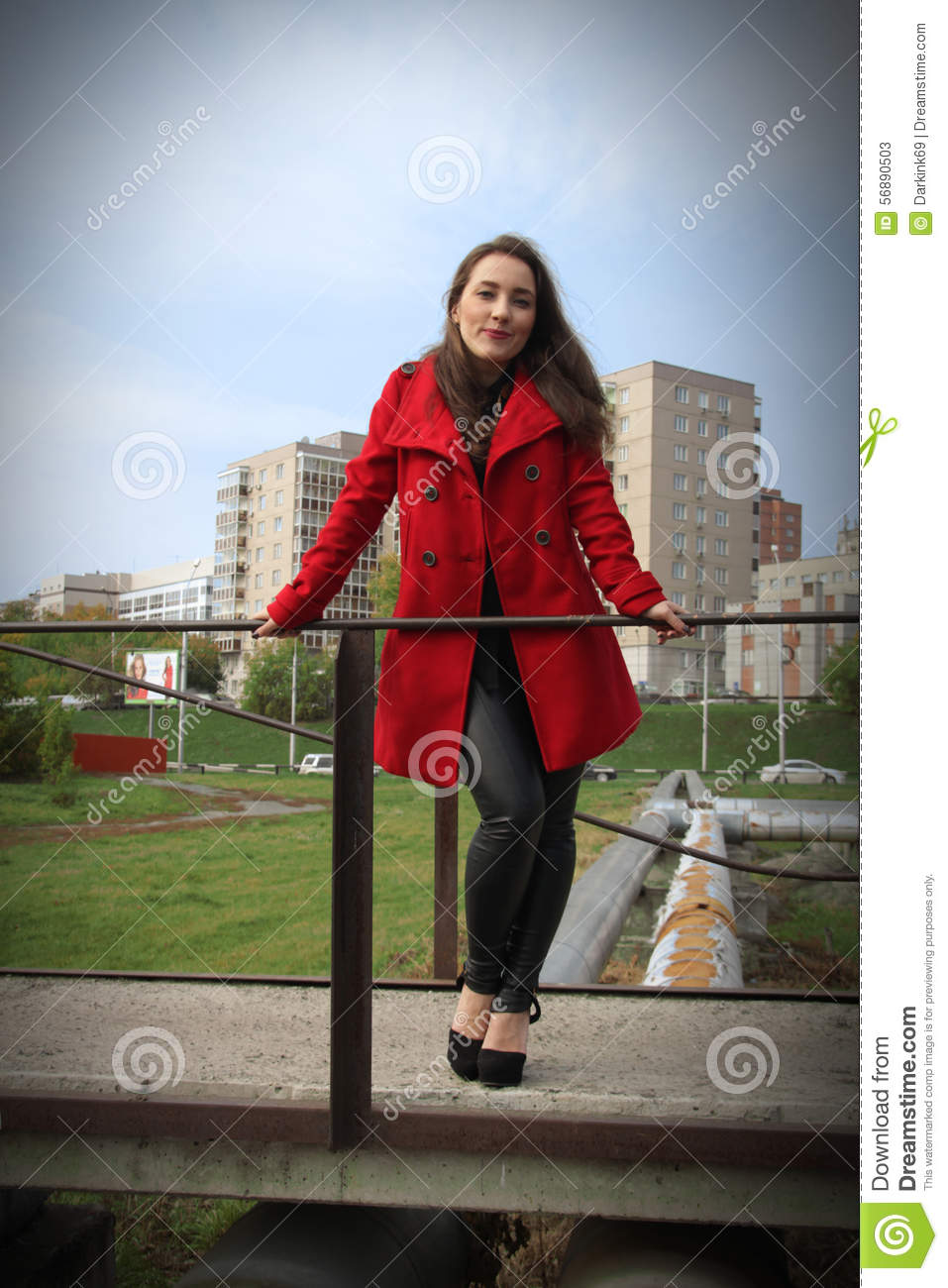 Beautiful Girl In A Red Coat Holding On To The Railing On Bridge ...