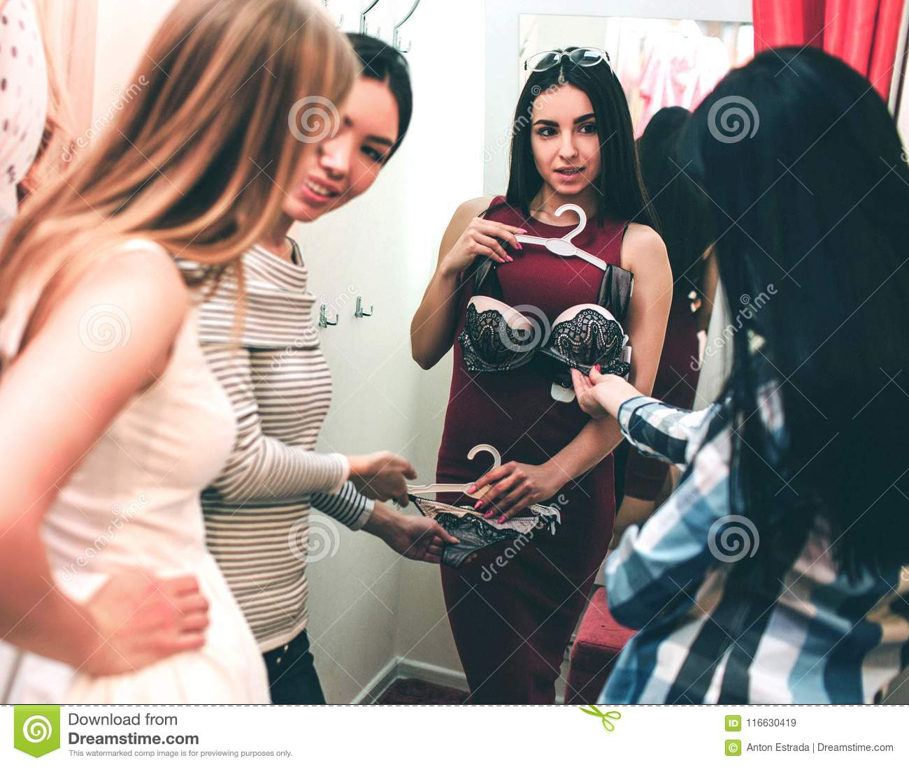 Beautiful girl in red dress is trying on herself bra. She is looking at her friends while they are looking at bra and
