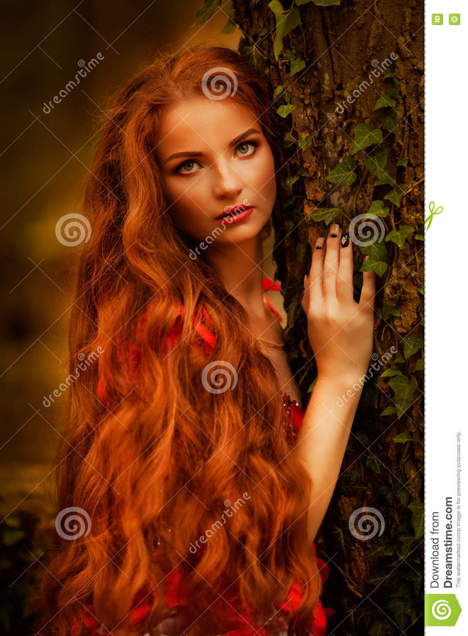 Beautiful girl with red hair in autumn park