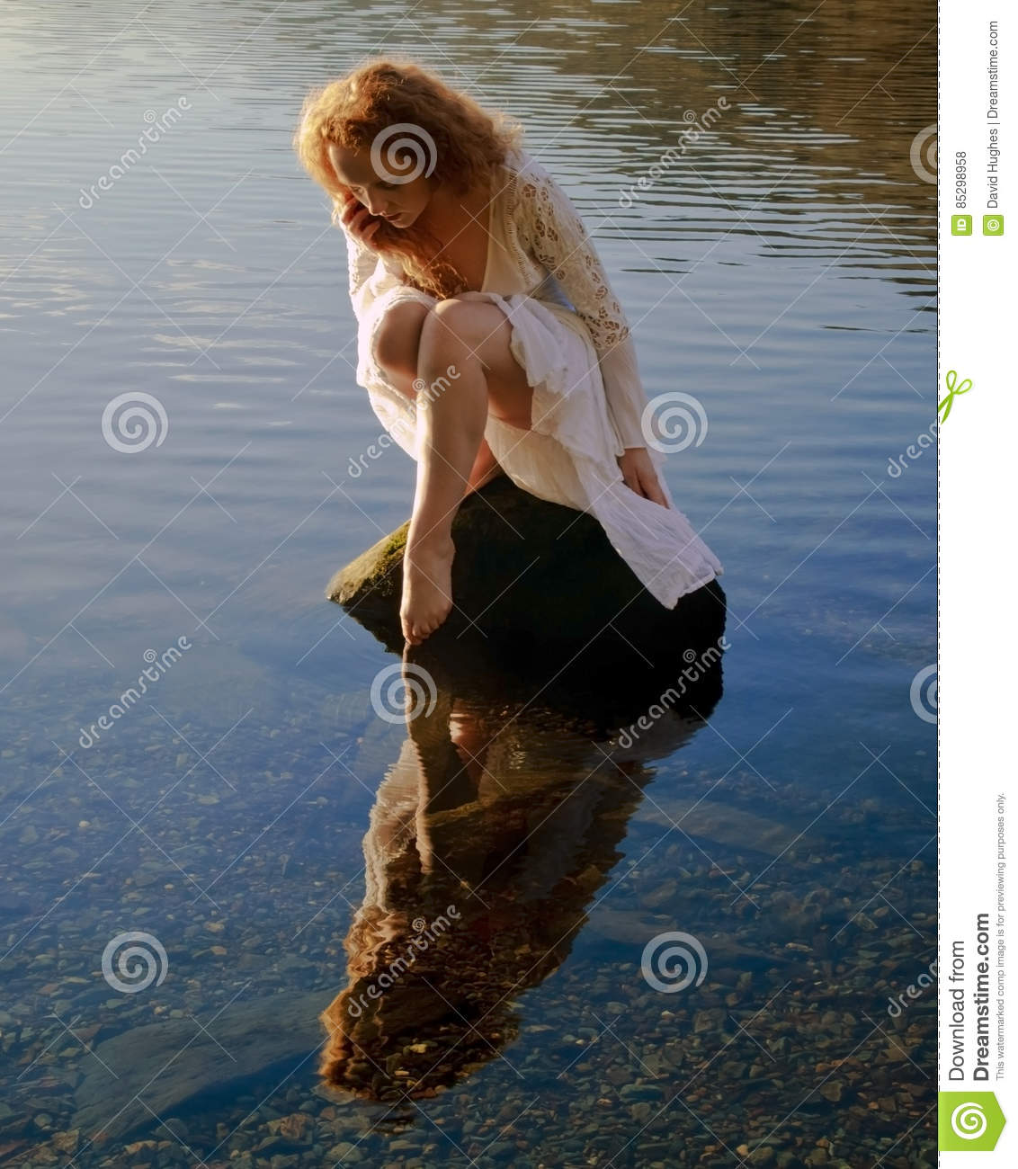 Beautiful girl with red hair reflected in ripples and still water