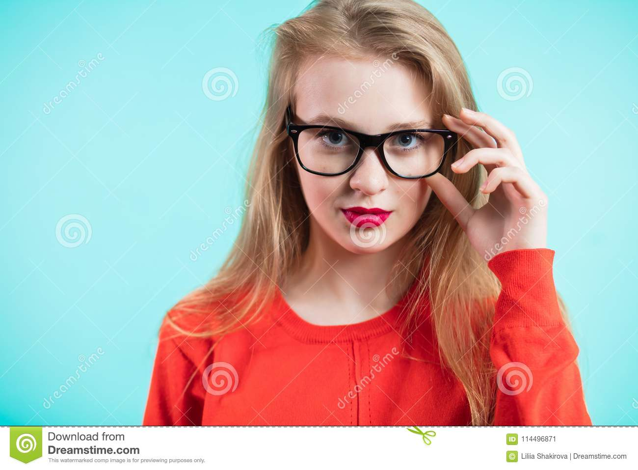 f70614810110 Beautiful girl red lips glasses black frames looking camera blue background  health good vision ophthalmology image