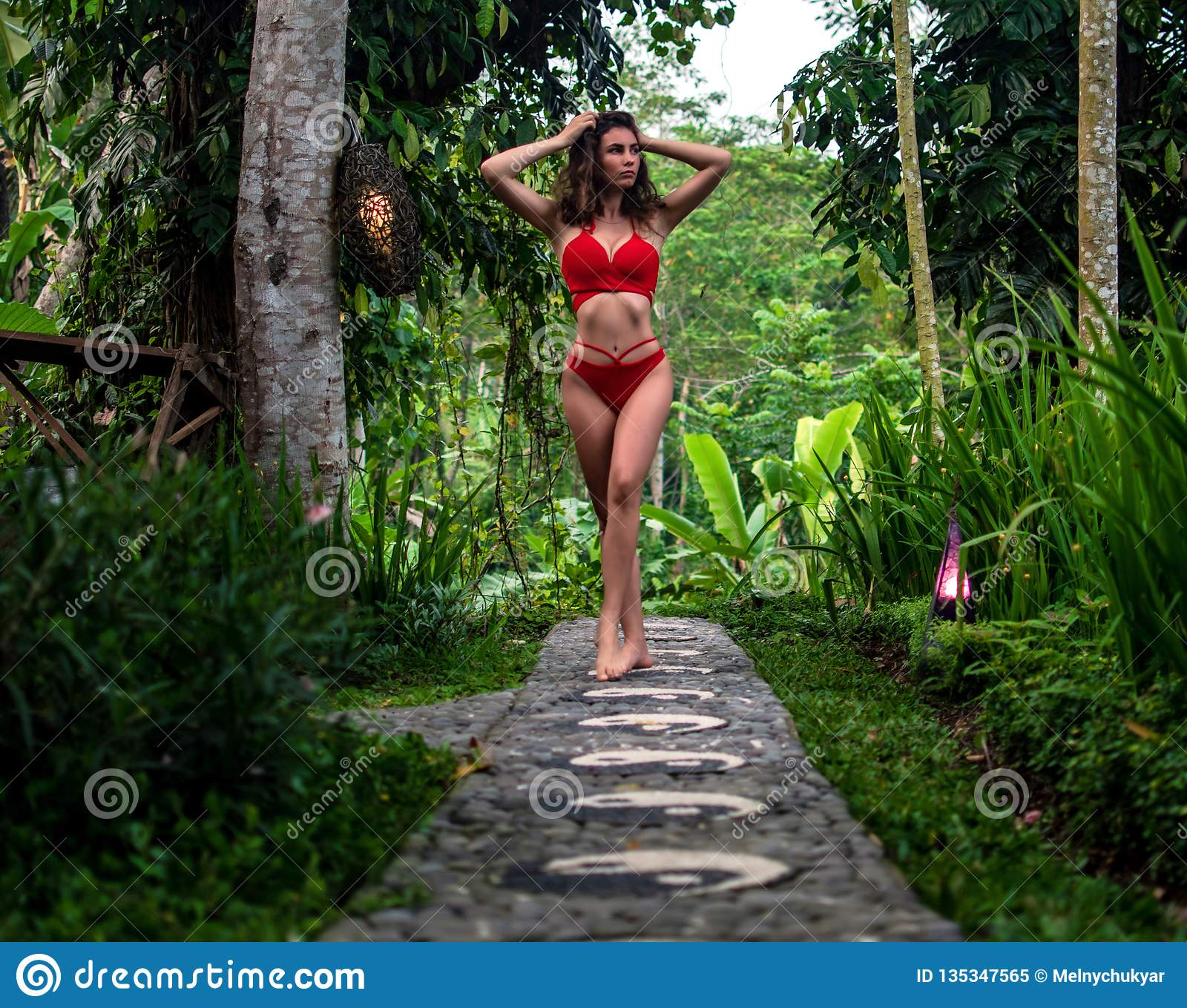 Beautiful girl in red swimsuit posing in tropical location with green trees. Young sports model in bikini with perfect