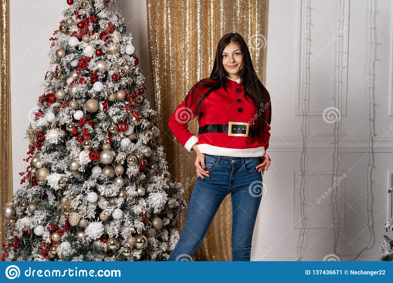 Beautiful girl in santa sweater after decorating the Christmas tree posing, looking at the camera