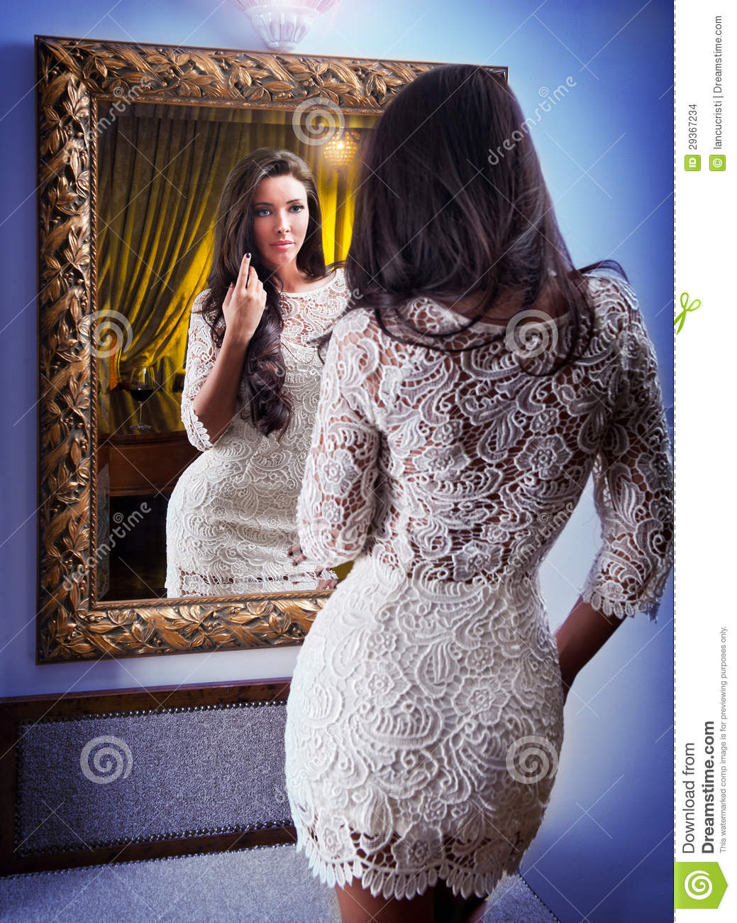The Beautiful Girl In A Short White Dress Looking Into Mirror ...