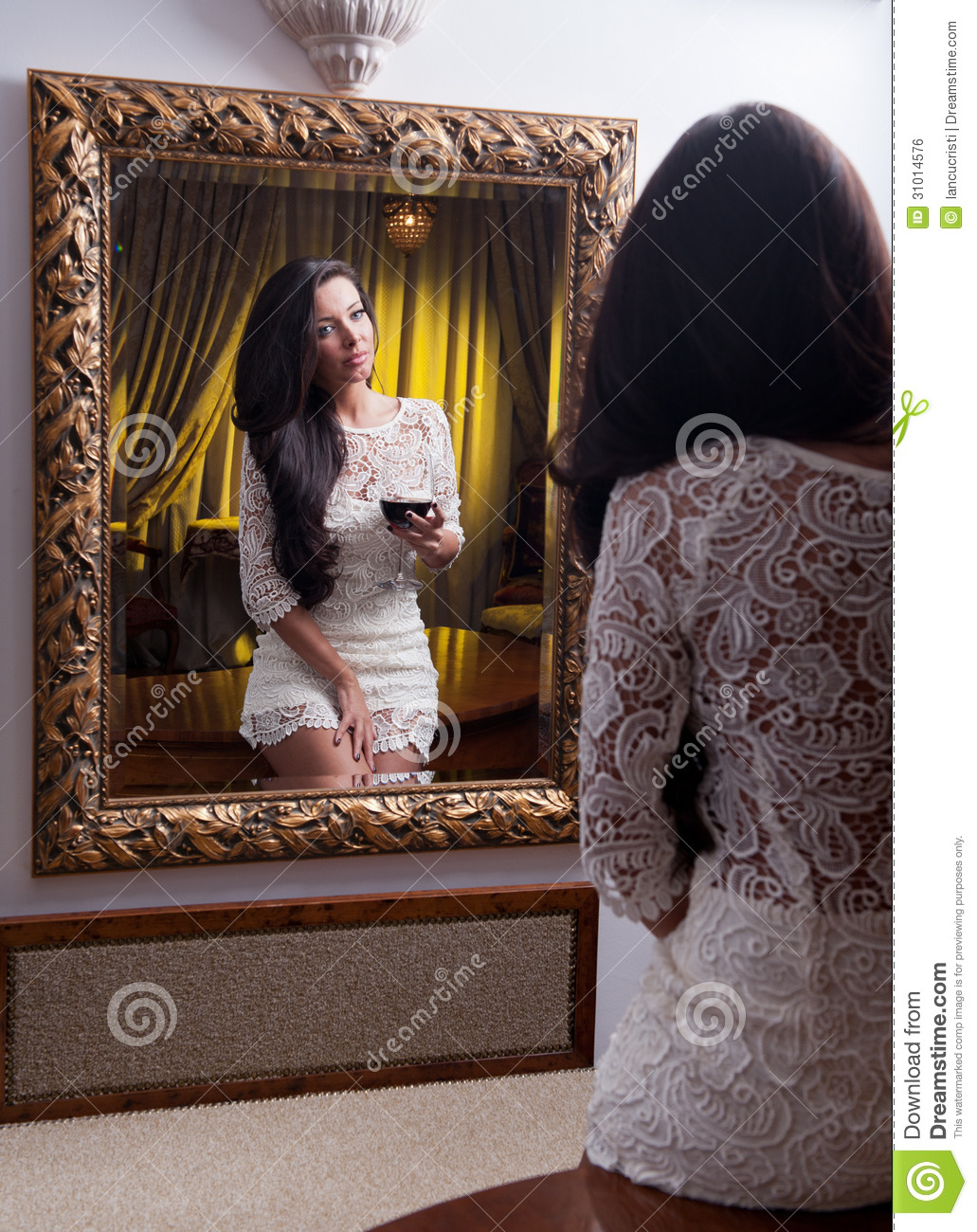 The beautiful girl in a short white dress looking into for Looking mirror