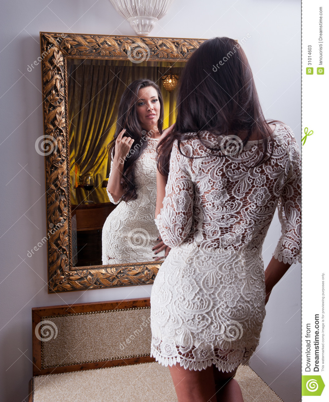 The beautiful girl in a short white dress looking into for Looking for mirrors