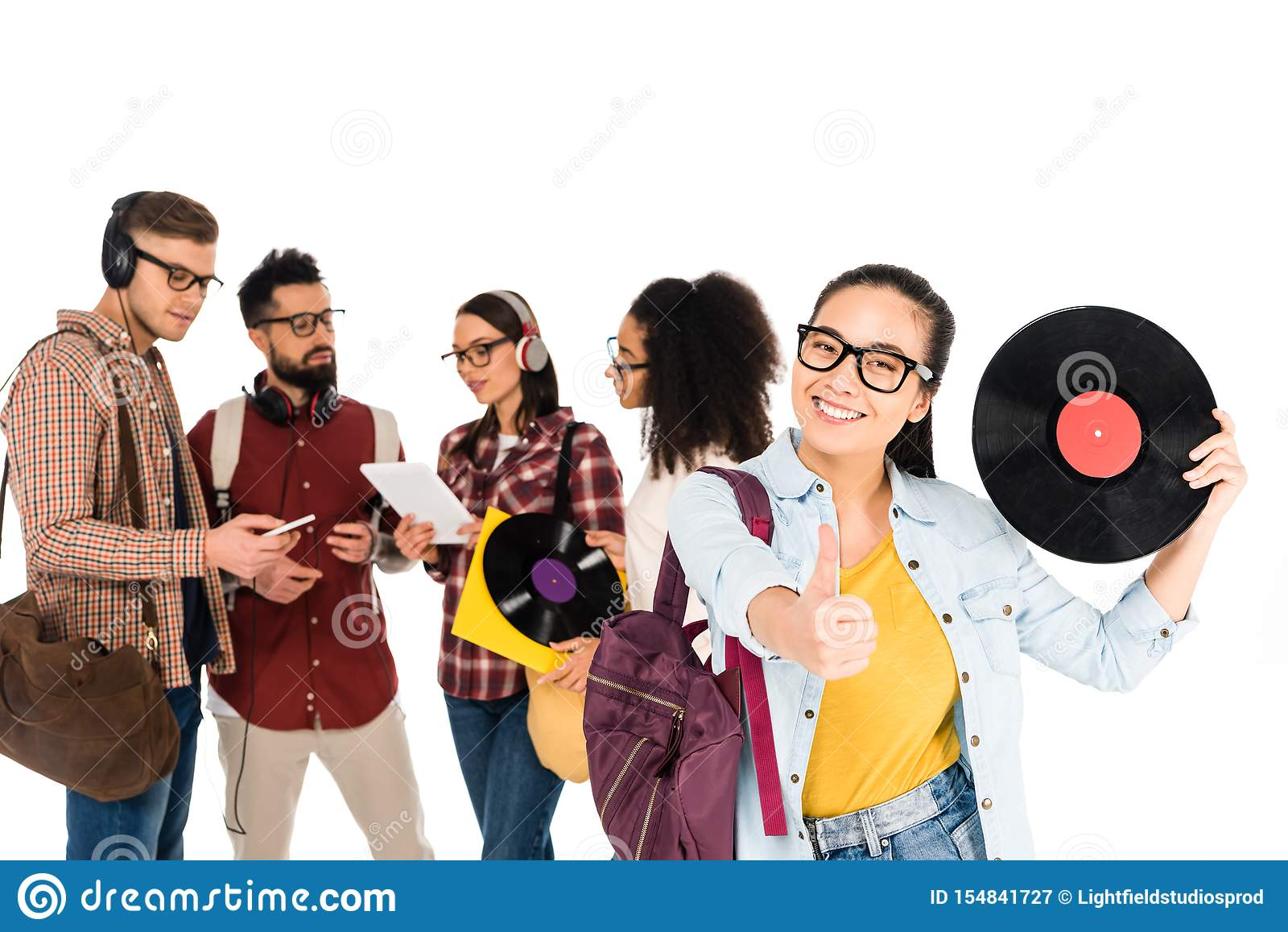 beautiful girl showing thumb up while holding vinyl record near milticultural group of people isolated