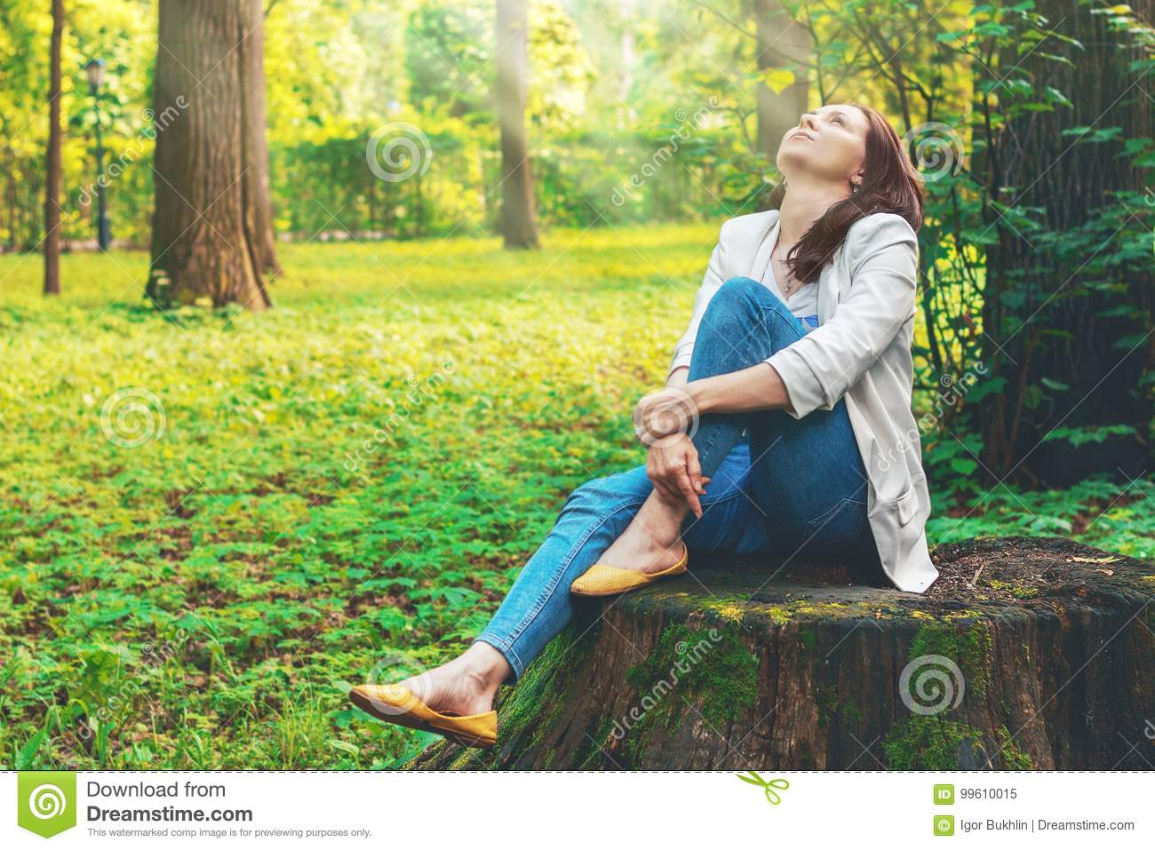 Cute woman is enjoying of picturesque nature. Camping, rest. Beautiful girl sits on a big old stump in the forest.