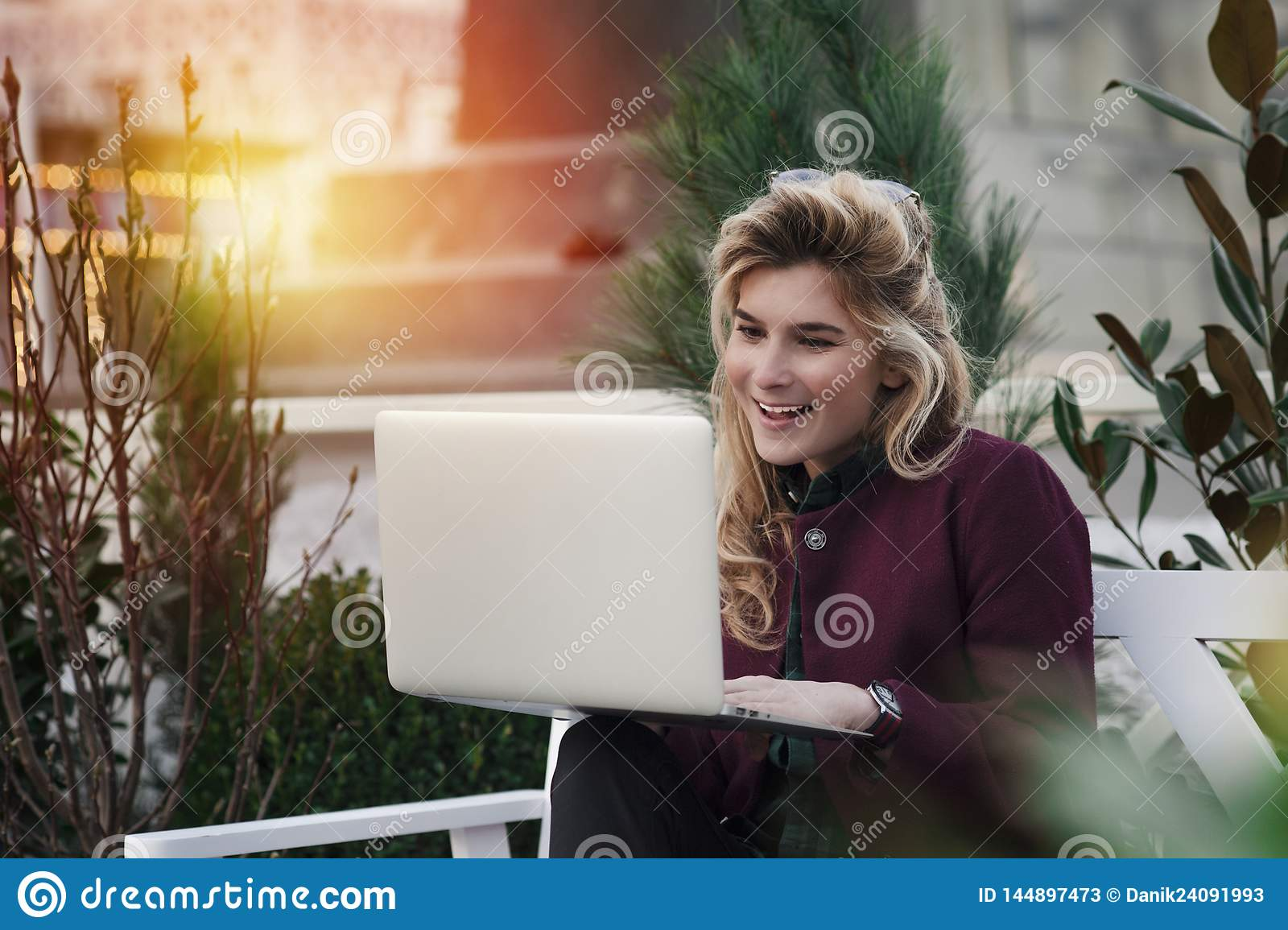 Beautiful girl is sitting on a bench with a laptop in her hands on a fresh street with the city. A concept work in pleasure,