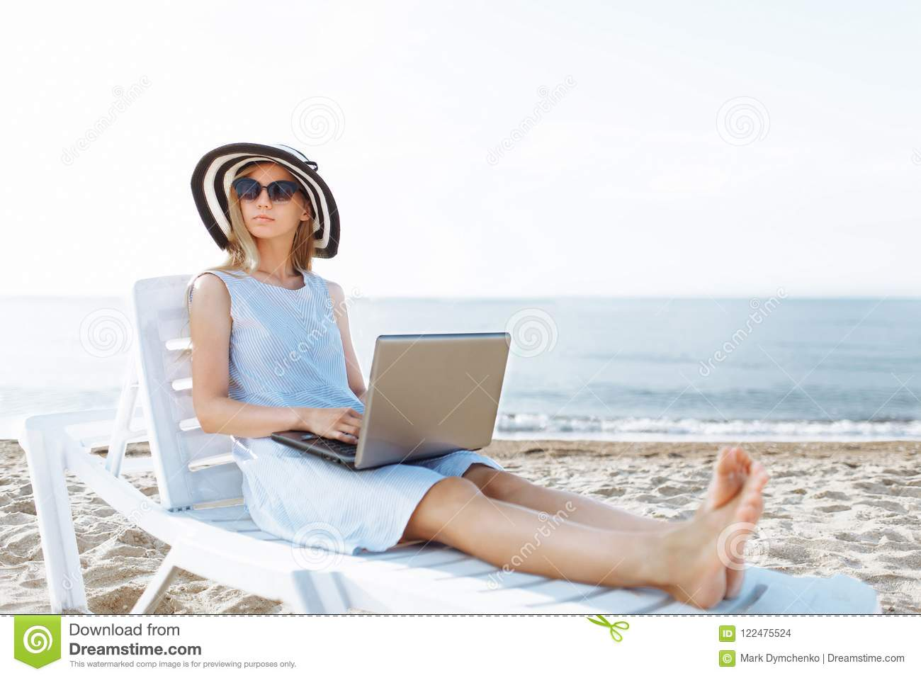 Beautiful girl sitting with a laptop on a chaise longue, a woman working on vacation, job search