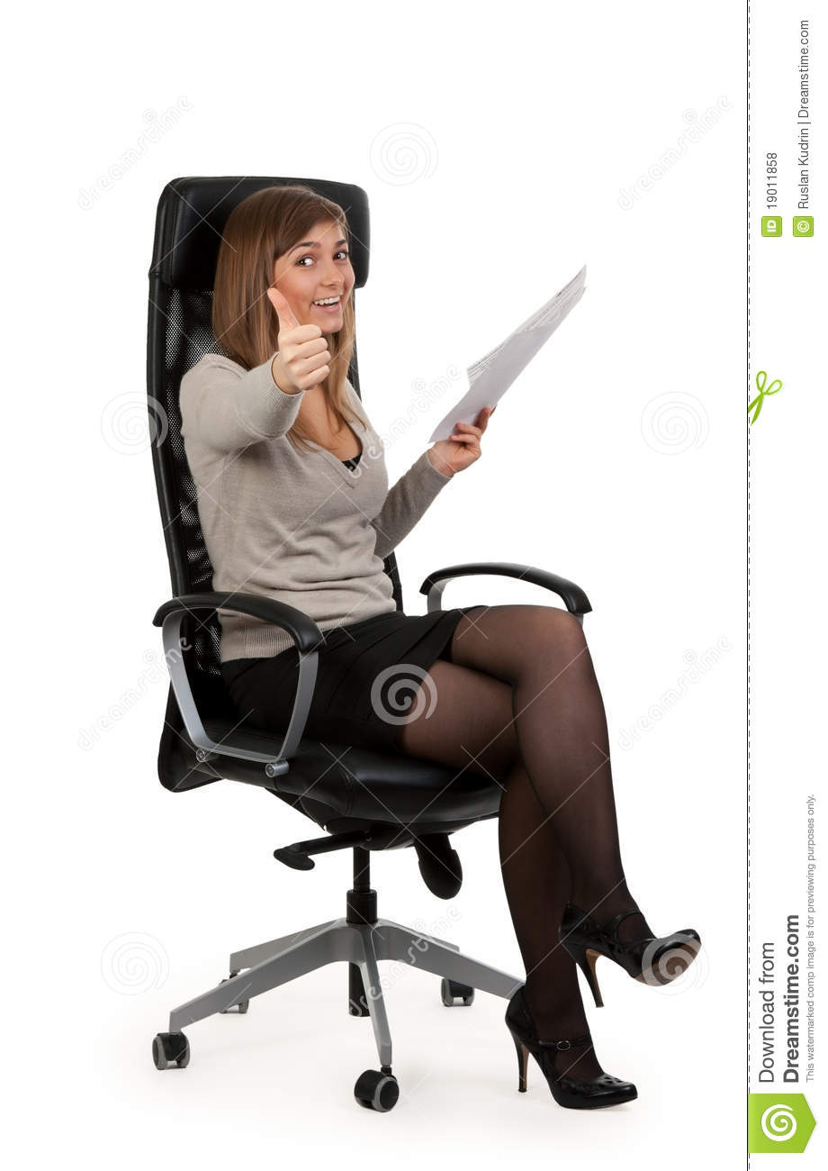 beautiful girl is sitting in an office chair royalty free stock photos