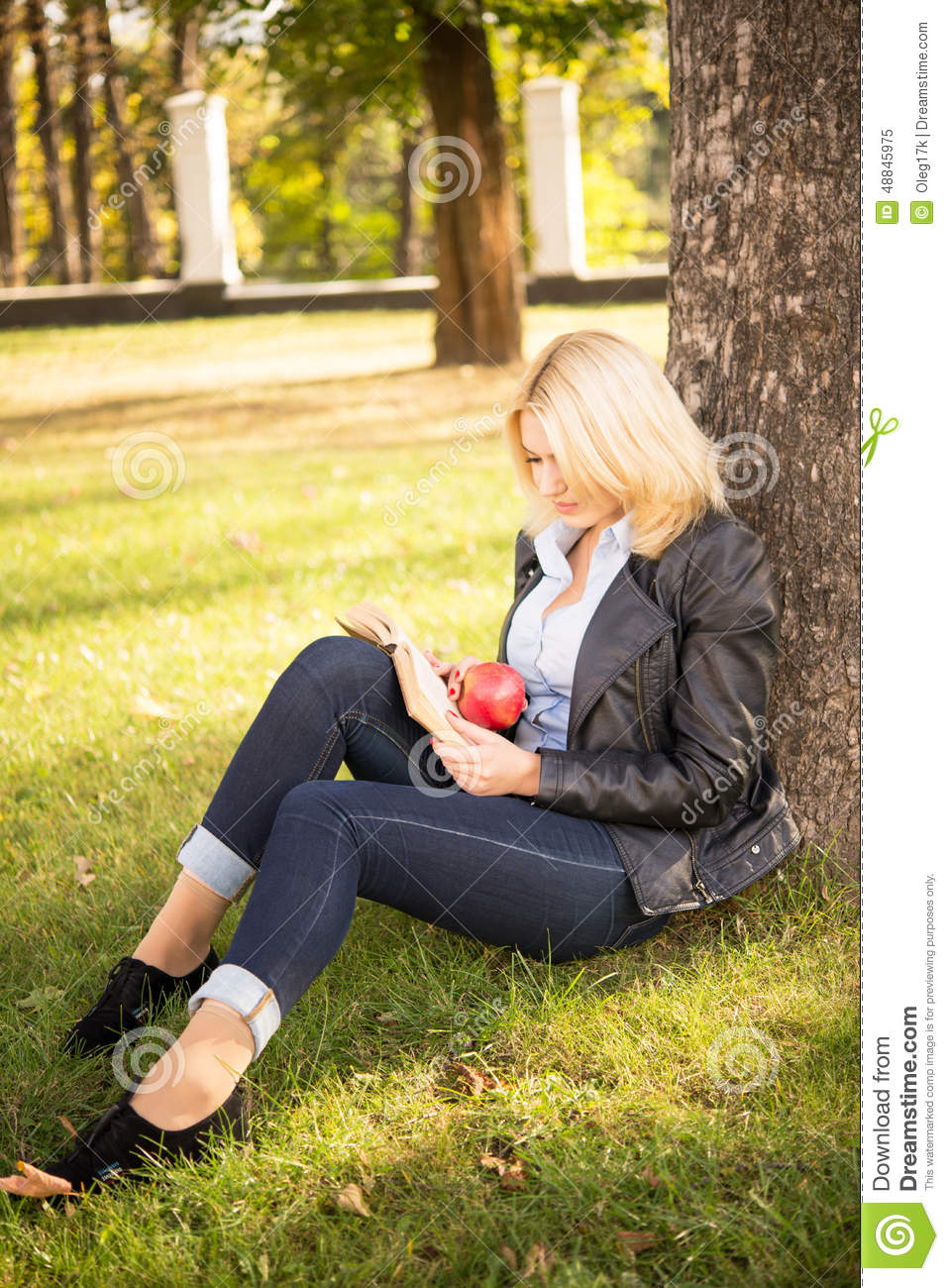 Beautiful girl sitting under a tree and reading a book