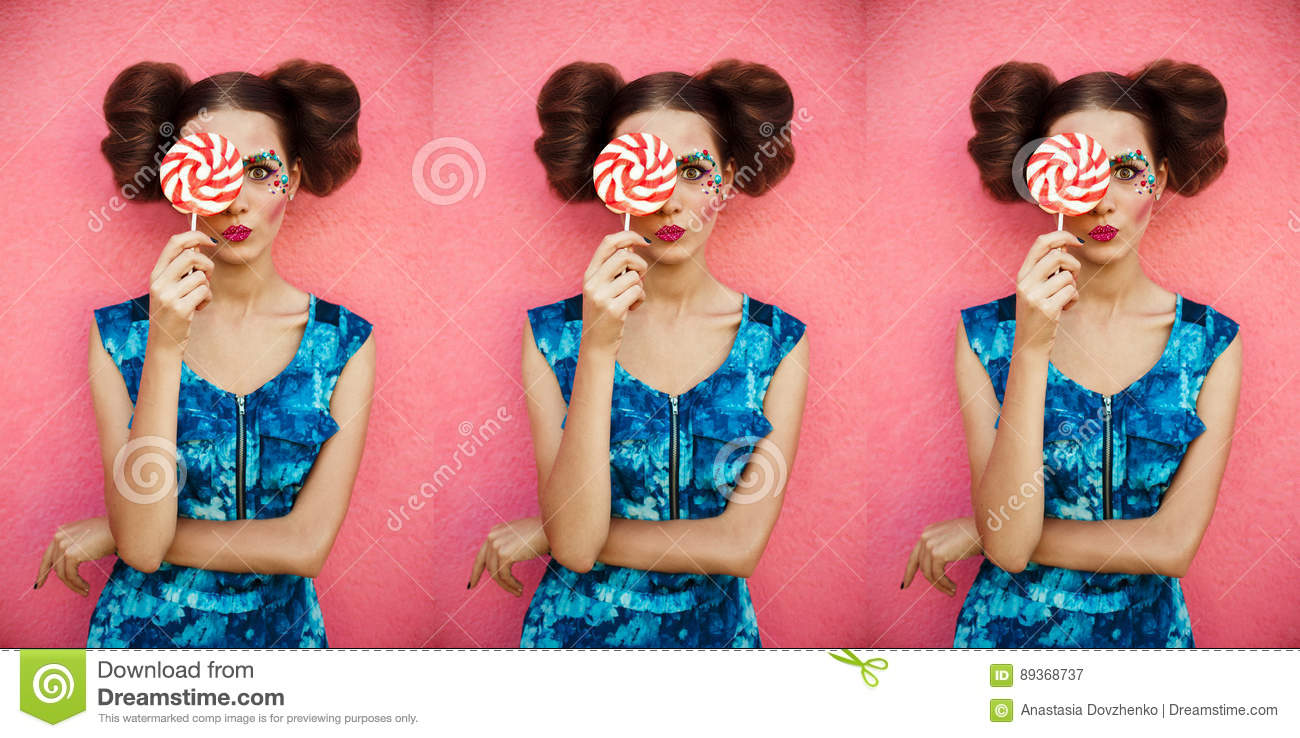 Beautiful girl standing against pink background with many sweet pink round lollipop hiding half of face. Fashion shot portrait.