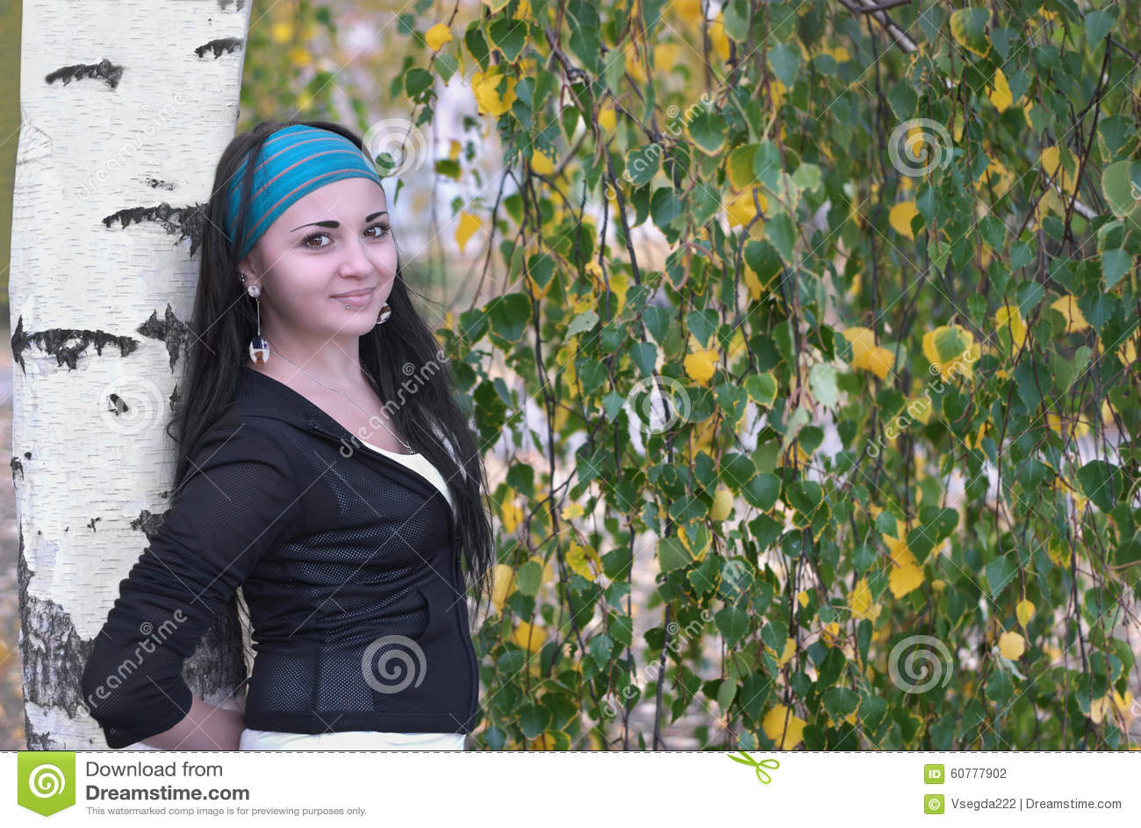 Beautiful girl standing alone near the birch.