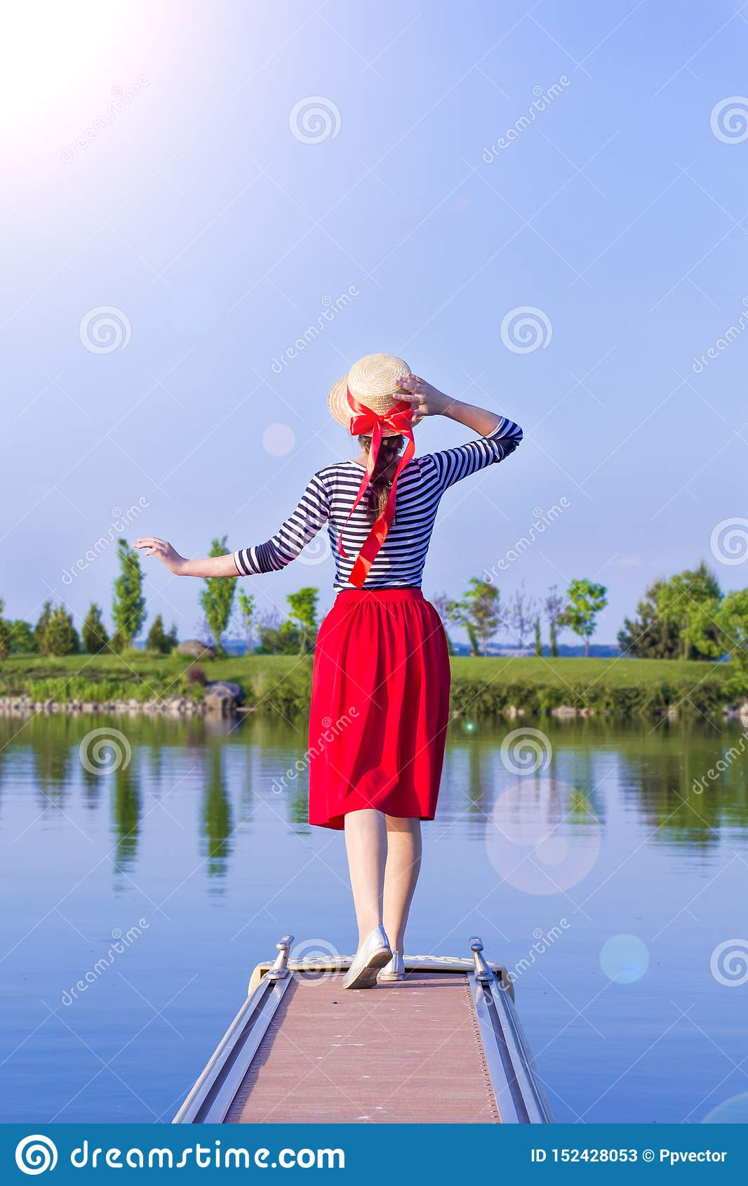 Beautiful girl in a straw hat on the pier from the back. Girl in a red skirt and a sailor suit on the pier at sunset