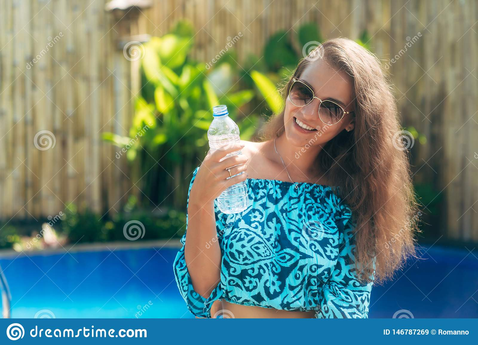 Beautiful Girl In Sunglasses And Blue Top Sits Near Swimming ...